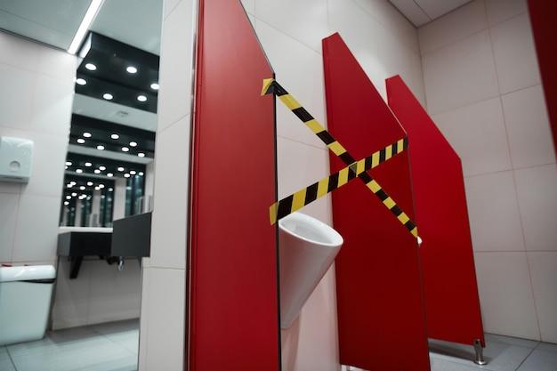 社会的距離と安全対策のためにトイレの屋台がテープで留められた、または故障した公共のバスルームのインテリアのグラフィック背景画像、コピースペース