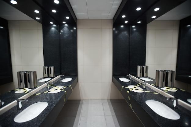 사회적 거리와 코비드 안전 조치를 위해 테이프를 붙인 세면대가 있는 공공 화장실 내부의 그래픽 배경 이미지, 복사 공간