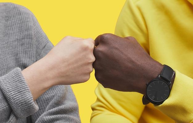 異人種間の友情と団結の概念、コピースペースを一緒に働いている間拳をぶつけている2人の現代のビジネスマンのグラフィックのクローズアップ