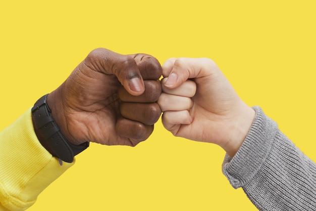 黄色の背景、異人種間の友情と団結の概念、コピースペースを照らすために拳をぶつける2人の若者のグラフィックのクローズアップ