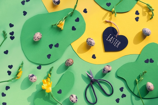 カラフルなグラフィックデザインのイースターの背景。フラット横たわっていた、ウズラの卵、はさみ、本文イースター、フリージアの花と心のトップビュー。