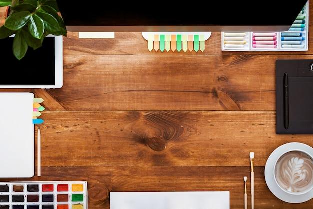 グラフィックの創造的なテーブルのコンセプト、茶色の木製の机の上のコンピューターの塗料