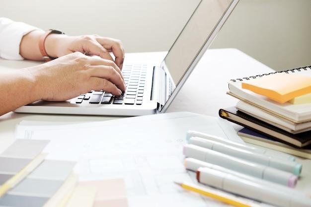 책상에 그래픽 디자인 및 색상 견본 및 펜. 작업 도구 및 액세서리로 건축 도면.
