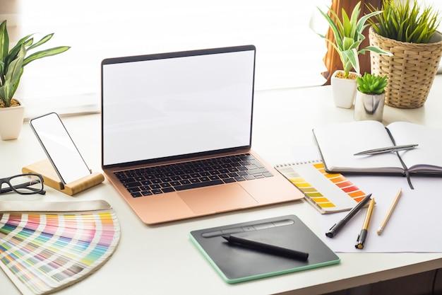 ノートパソコンの空白の画面とグラフィックデザインスタジオ