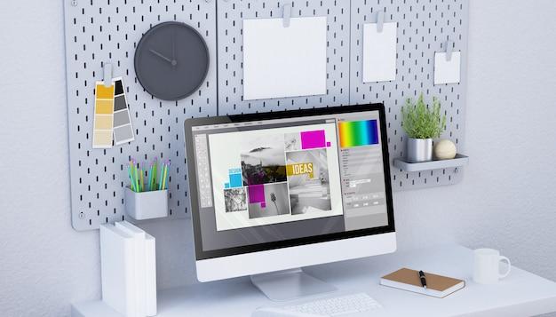 コンピュータを備えたグラフィックデザインスタジオペグボードのモックアップにぶら下がっている別の紙