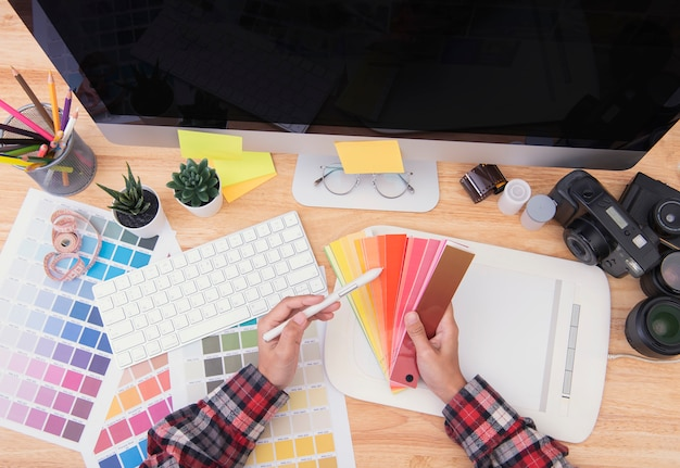 Graphic designer artist creative looking at colour chart at desk in office.