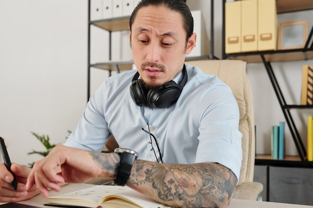 Graphic designer checking watch on his wrist after working on project for many hours