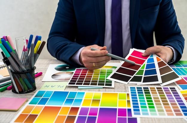 사무실의 샘플러에서 색상을 선택하는 그래픽 디자이너. 색상 견본. 샘플러에서 색상을 선택하는 사람 손