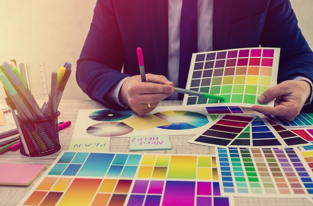 Graphic designer choosing a color from a sampler at office. color swatches. man hands choosing a color from an sampler
