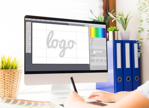 Графический дизайнер, разрабатывающий логотип на компьютере