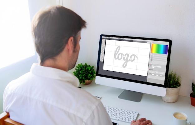 コンピューターでロゴをデザインするグラフィックデザイナー。