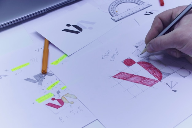 Graphic designer designs a logo against a background of sketches and drawings on a table. printed logos on paper in a studio with a laptop.