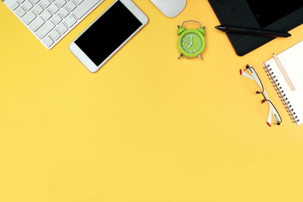 Graphic designer desk top view with computer on yellow