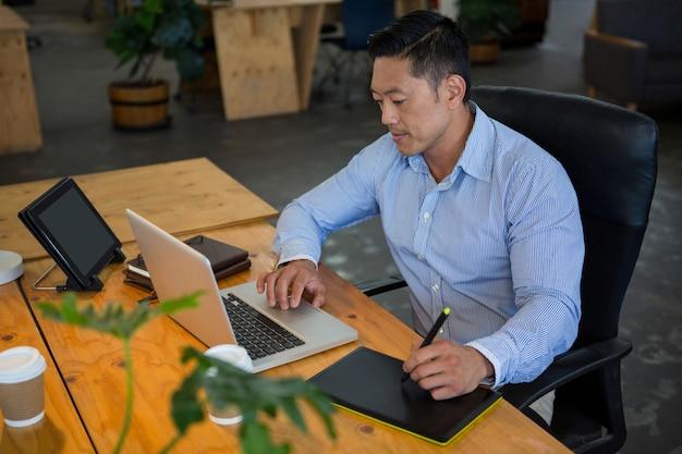 Графический дизайнер, опираясь на графический планшет при использовании ноутбука