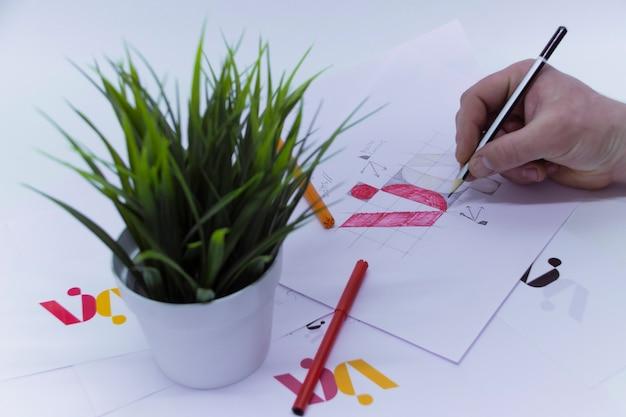 그래픽 디자이너는 냄비에 꽃이 있는 밝은 배경의 크리에이티브 스튜디오에서 로고를 그리고 프린트를 그립니다.