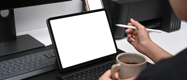 Графический дизайнер пьет кофе и работает с планшетным компьютером в творческом офисе.