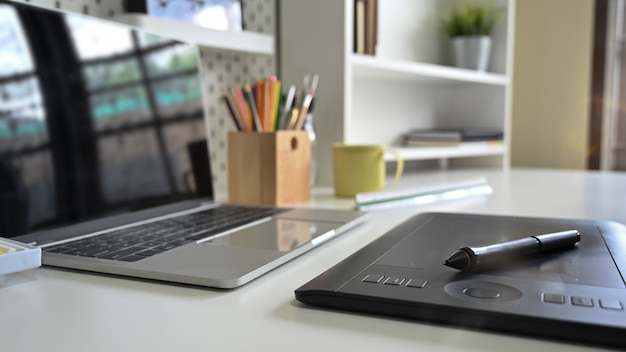 Graphic designer equipment with stylish pen and tablet with computer on creative table.