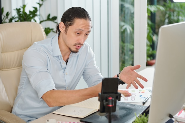 Graphic designer filming himself explaining how to create great company logo for online school