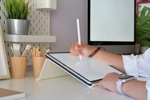 스튜디오에서 디지털 드로잉 스케치 태블릿 펜을 사용하여 그래픽 디자이너 손