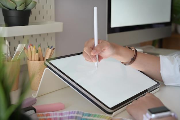 스튜디오에서 디지털 태블릿 펜을 사용하는 그래픽 디자이너 손