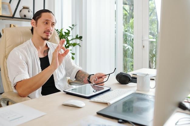 Графический дизайнер проводит онлайн-встречу с клиентом, когда они обсуждают детали нового проекта