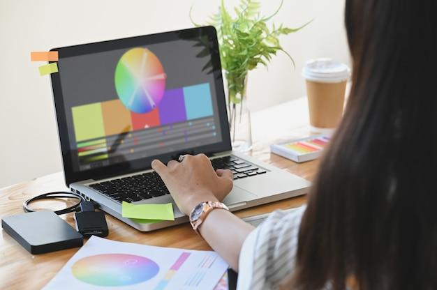グラフィックデザイナー彼女はラップトップとテーブルの上の創造的なアクセサリーで色を選択します。