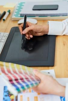 グラフィックタブレットでデジタを使って絵を描くときにカラーサンプルのパレットを保持しているグラフィックデザイナー...