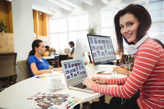 Графический дизайнер, глядя на камеру во время коллега работает в ба
