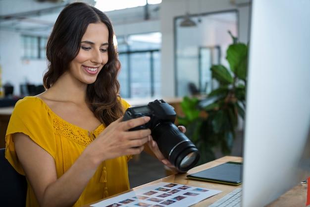 Графический дизайнер, глядя на фотографии в цифровой камере