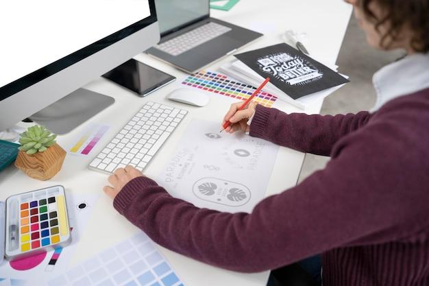 노트북에 로고를 만드는 그래픽 디자이너