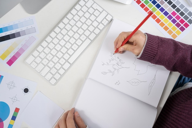 Graphic designer making a logo on a notebook