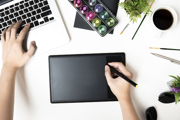 Graphic designer man is working on white office desk. top view, flat lay.