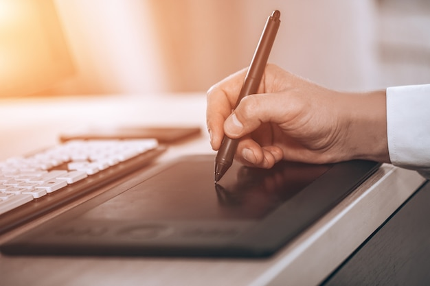 Graphic designer's workspace. hand on pen tablet. young smart man in the office. free black monitor copy space for design. warm glare of sun light