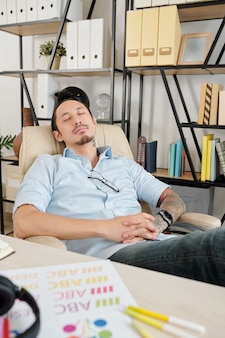 Graphic designer sleeping in chair at his home office when having short break after working on company logo for client