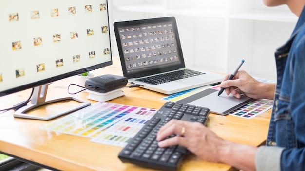 Команда графического дизайнера работает над веб-дизайном, используя образцы цветов, редактируя обложки, используя планшет и стилус at desks in busy creative office.