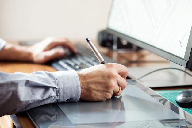 Графический дизайнер, использующий цифровой планшет и компьютер в офисе или дома