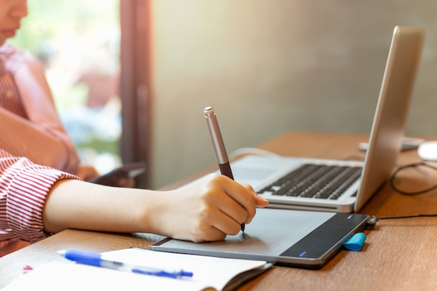 Графический дизайнер, с помощью цифрового планшета с ноутбуком на столе.