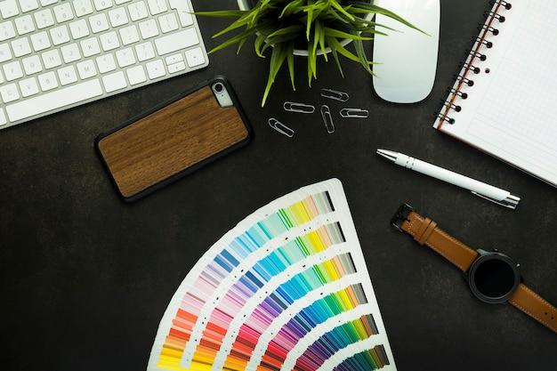 黒い机とキーボード、植物、マウス、メモ帳、スマートフォン、ペンを備えたグラフィックデザイナーのワークスペース