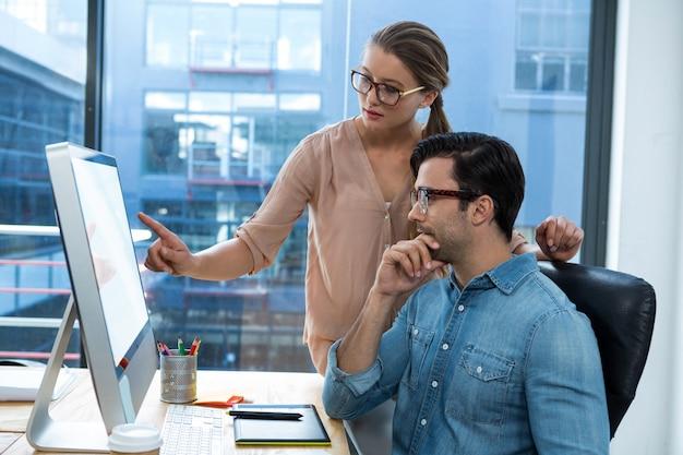 Графический дизайнер, работающий за столом с коллегой
