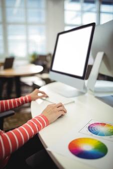 그녀의 책상에서 일하는 그래픽 디자이너