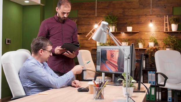 ゲーム業界で働くグラフィックデザイナーが、レベルの環境について話し合っている同僚に新しい仮想ゲームデザインを見せています。クリエイティビティオフィスで3dビデオゲームを開発するゲーム制作チーム