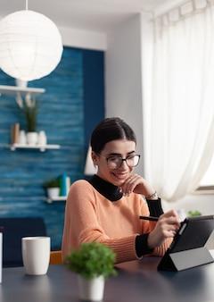 引き出しペンを手に持ってドローをレタッチするグラフィックデジタルタブレットを使用してクリエイティブなイラストに取り組んでいるグラフィックデザイナー。居間の机のテーブルに座っている集中学生