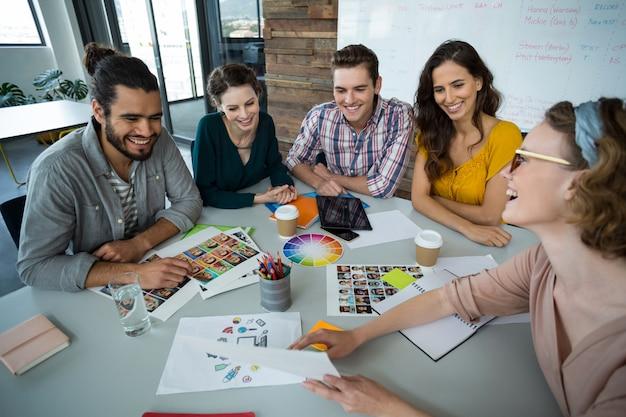 Графические дизайнеры обсуждают друг с другом на встрече