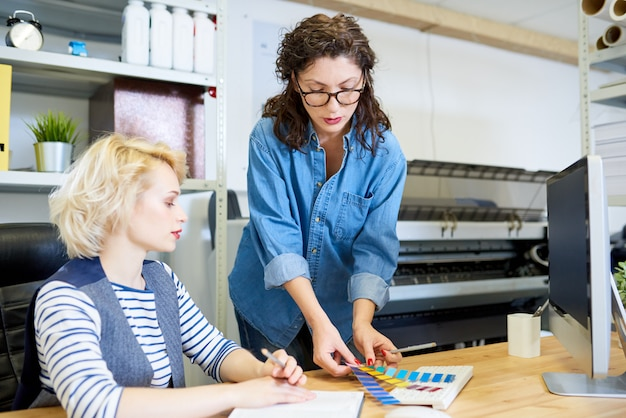 Graphic designers in printing shop