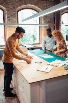 グラフィックデザイナー。製紙プロジェクトに取り組んでいる才能のあるグラフィックデザイナーのチーム