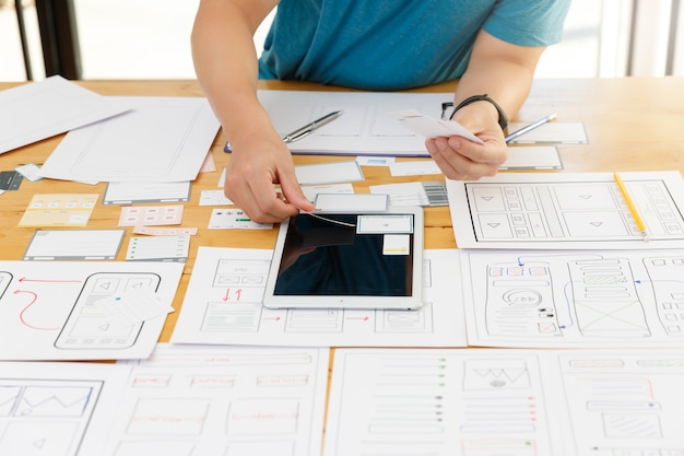 Graphic designers work together with ux ui designer planning application template layout framework for mobile phone computer mobile