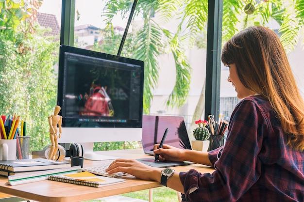 グラフィックデザイナーは、コンピュータとマウスのペンデザイン製品とウェブサイトで作業する