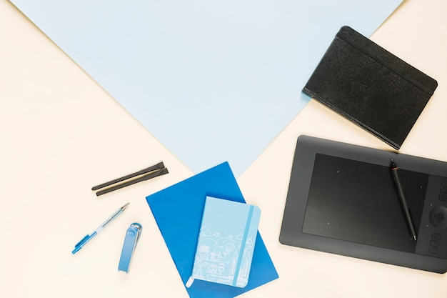 Graphic digital tablet with various stationeries on colorful paper backdrop