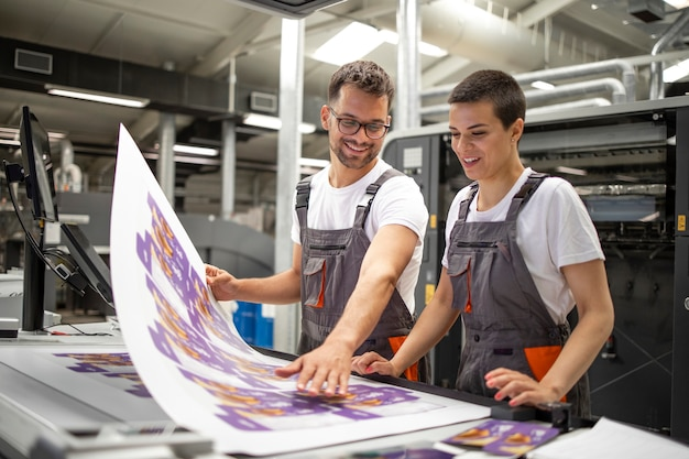 Графические инженеры или рабочие проверяют качество отпечатков в современной типографии.
