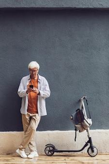 Графический портрет в полный рост модного пожилого мужчины, использующего смартфон на открытом воздухе, стоя у электрического скутера